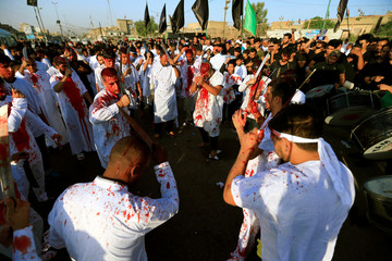 Iraqi Shi'ite Muslims bleed after hitting their foreheads with swords and beating themselves during the religious festival of Ashura in Baghdad