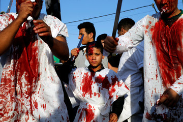 An Iraqi Shi'ite Muslim boy gashes his forehead with a sword during a ceremony marking Ashura in Baghdad's Sadr City