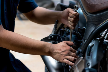 People are repairing a motorcycle Use a wrench and a screwdriver to work. Use the wrench to tighten the cylinder.