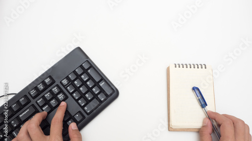 Wall mural Office desk table with keyboard black and notebook Top view on white background