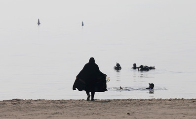 A Saudi female diver wearing an abaya carries snorkels as she makes her way to swim in Half Moon Beach open-water dive site in Dhahran
