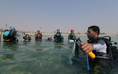 Diving instructor gives a briefing to Saudi female divers at Half Moon Beach open-water dive site in Dhahran
