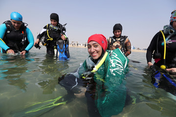 Saudi female diver smiles as she wears Saudi national flag over her shoulders as she enters the sea to dive at Half Moon Beach open-water dive site in Dhahran