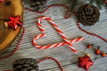 New Year on Valentines day , Candy canes,cinnamon stick in a heart shape on a wooden background and small homemade boxes with gifts