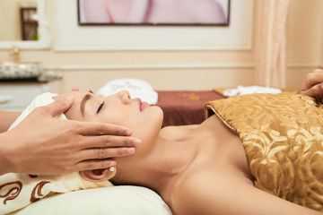 Beautiful young woman getting face massage in spa salon