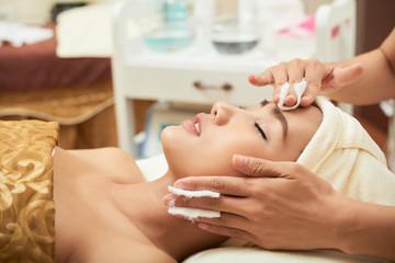 Vietnamese young woman enjoying facial in spa salon