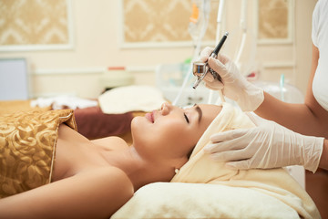 Cosmetologist using professional apparatus for rejuvenation in beauty salon