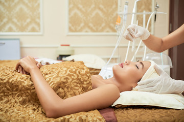 Cosmetologist using professional apparatus for microdermabrasion of patient
