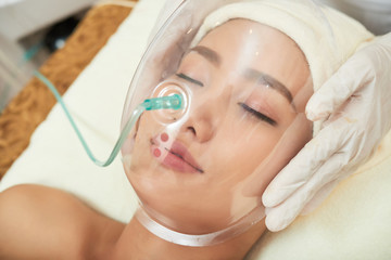 Face of beautiful young Vietnamese woman in plastic mask for spa sprocedure