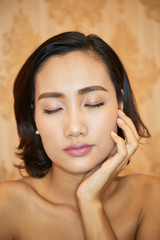 Beautiful young Asian woman with perfect skin standing with her eyes closed