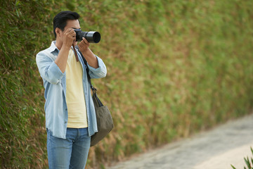Professional photographer with digital camera taking photos outdoors