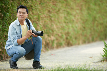 Handsome young Vietnamese woman with professional camera working outdoors