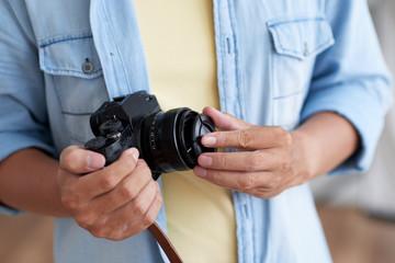 Hands of photographer putting lens cap on digital camera