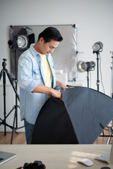 Technician preparing equipment for shooting in studio
