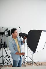 Photographer assistant setting lighting equipment in studio