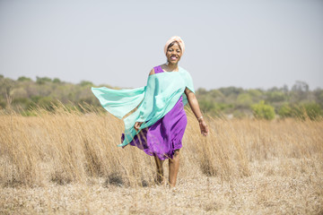 African women with purple dress walking in field