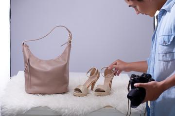 Photographer putting heels and purse on fur rug to make fashion blog post