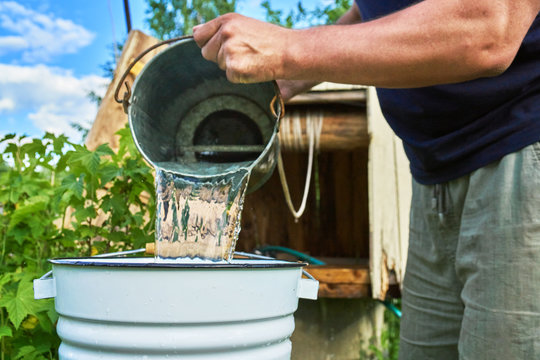 Man pouring water just taken up from a well into a enameled bucket