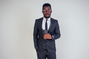 Handsome young African man in formal black suit holds a plastic paper cup with hot coffee cocoa (tea) to go . businessman on coffee break after meeting on white background in studio