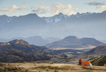 hiker at Chacabuco Valley with a view over the Jeinimeni Mountain peaks, Parque Patagonia, Aysén Region, Chile.
