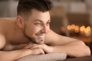 Young man relaxing on massage table in spa salon