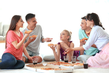 Young people having fun at party with delicious pizza indoors