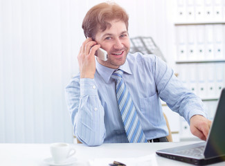 handsome businessman sitting at Desk and talking on a cell phone