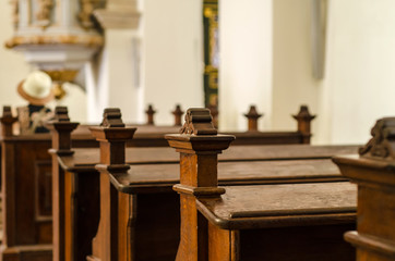 Brown wooden benches in a Catholic temple, close-up