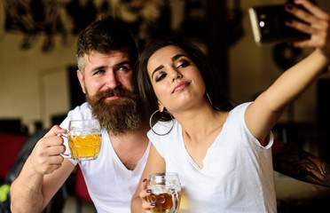 Couple in love on date drinks beer. Man bearded hipster and girl with beer glass full of craft beer. Best friends or lovers drinking beer in pub. Take selfie photo to remember great date in pub