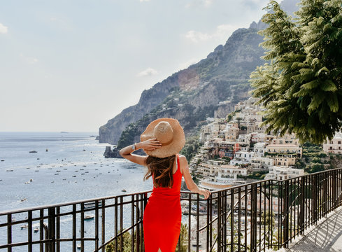 beautiful woman with long dark hair in elegant dress and straw hat traveling in Italy