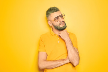Portrait of handsome man with dyed hair and beard on color background