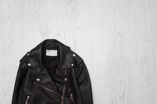 Black leather jacket close-up on a wooden background