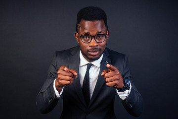 afro american business advisor man pointing with finger to the camera and to you, hand sign confident gesture from the front black background in studio