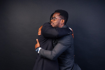 two business partners hugging in the studio on a black background