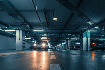 Large hall with columns of underground car parking garage with many automobiles in modern mall or shopping center inside