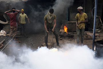 A worker moves a piece of hot iron as he works at a dockyard in Dhaka
