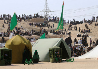 Iraqi people behind tents watch the local actors dressed as ancient warriors re-enact a scene from the 7th century battle of Karbala to commemorate Ashura in Najaf