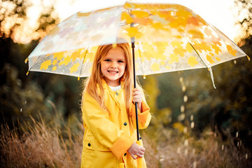 Happy funny child with umbrella under the autumn shower. Girl is wearing yellow raincoat and enjoying rainfall. Kid playing on the nature outdoors. Family walk in the park.