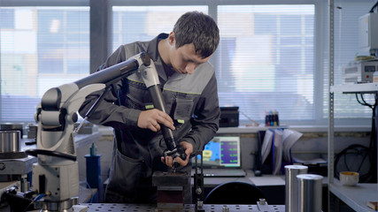 Manufacture of metal parts. A laboratory specialist measures the physical characteristics of a product.