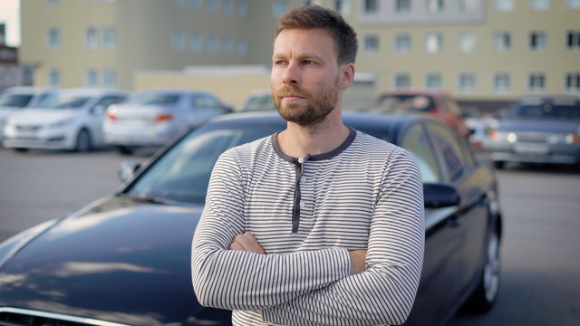 pensive serious man is standing on open parking area in summer day, crossed hands on chest and looking in distance