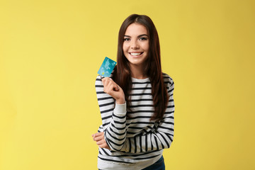 Young woman with credit card on color background. Online shopping
