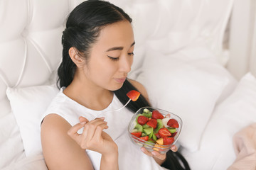 Asian woman eating healthy fruit salad for breakfast at home