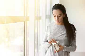 Young woman with wallet full of money standing near window