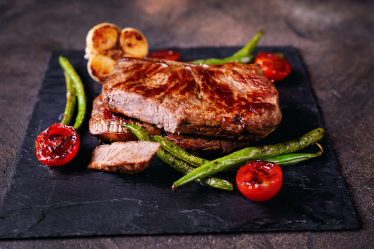 Delicious grilled steaks with vegetables on slate plate