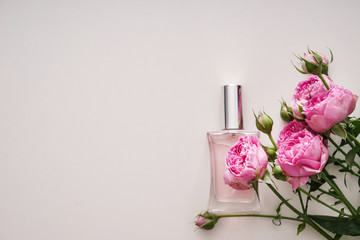 Bottle of perfume with beautiful flowers on white background