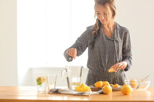 Young woman preparing fresh lemonade at home