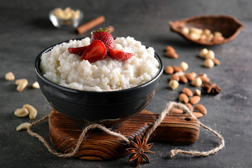 Bowl with delicious rice pudding and strawberry on dark table