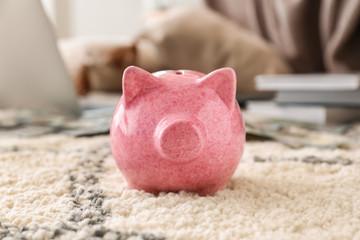 Piggy bank on soft carpet indoors