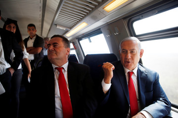 Israeli Prime Minister Benjamin Netanyahu sits next to Israel's Transportation and Intelligence Minister Katz during a test-run of the new high-speed train between Jerusalem and Tel Aviv, near Lod
