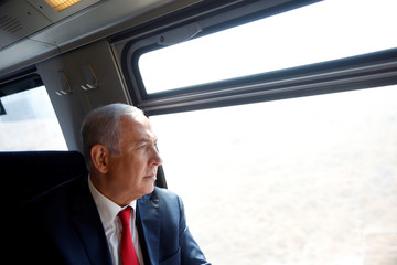 Israeli Prime Minister Benjamin Netanyahu looks out a train window as he participates in a test-run of the new high-speed train between Jerusalem and Tel Aviv, near Lod